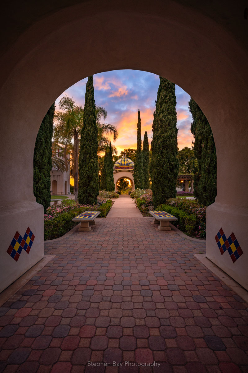 Secret Garden is a photo of a pathway in Balboa Park leading into a colorful sunset. The pathway is framed by an arch.
