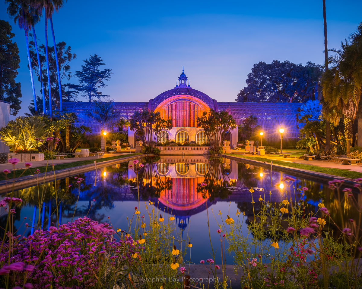 Botanical Building and lily pond in the early morning hours. There are flowers in the foreground and a reflection of the botanical building in the water.