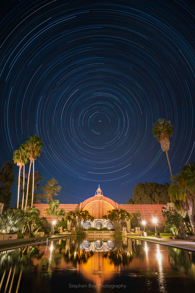 Star trails over the Botanical Building in Balboa Park. In the foreground is the lily pond with a few ducks. The star trails make concentric circles in the sky.