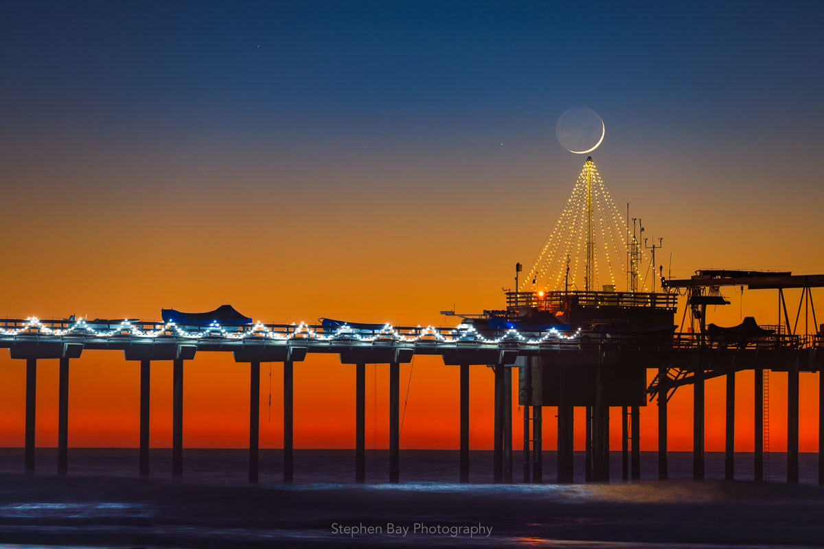 A crescent moon setting over the Christmas Tree at Scripps Pier. The moon is just above the top of the tree.