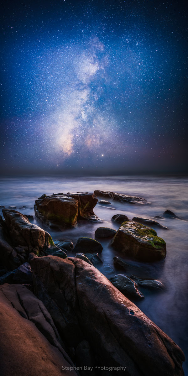 A vertical panorama of the coastline at Windansea Beach in La Jolla at night. The foreground has a number of sandstone rocks with the ocean water swirling around. The sky shows the stars of the Milky Way galaxy and the central core.