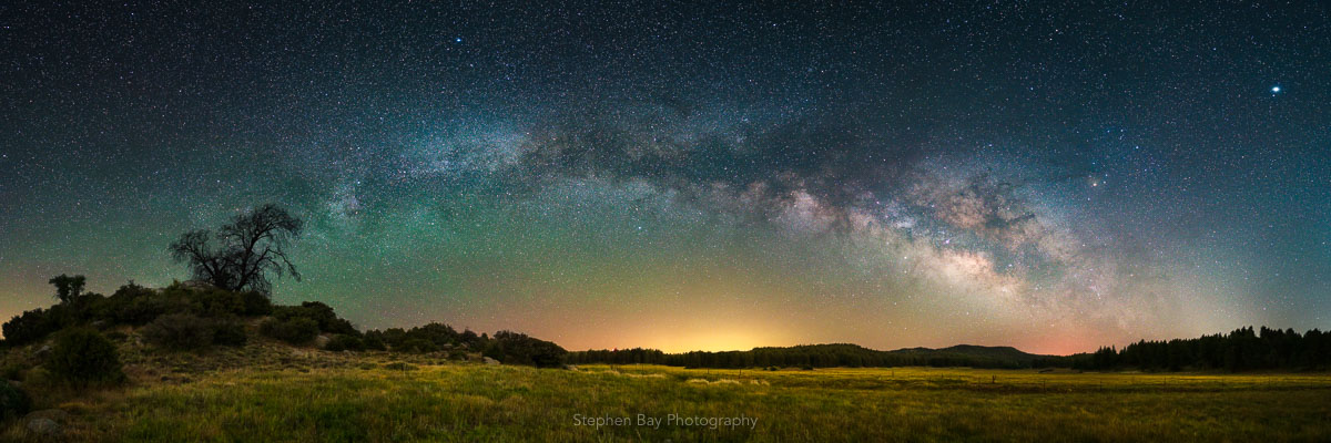 This is a panorama showing the full arch of the Milky Way over a meadow in the Cleveland National Forest.
