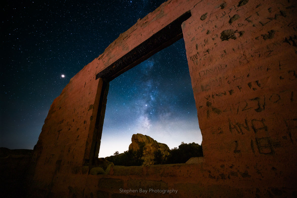 The remains of an abandoned house. There is one wall left standing with an opening for a window. In the center of the window the core of the Milky Way can be seen.
