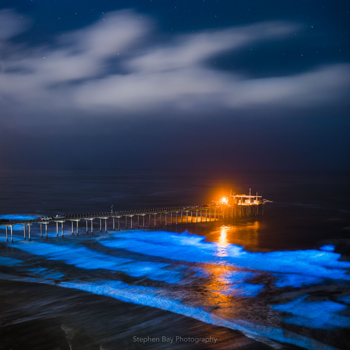 A photo of scripps pier with glowing blue waves from bioluminescent algae washing on to shore. The photo is at night with white clouds and stars in the sky.
