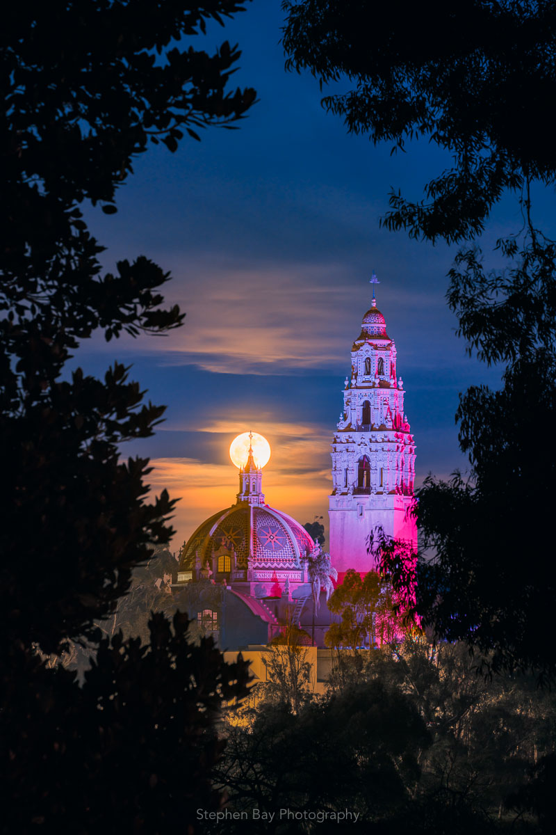 Moonlight Triumph is an artwork showing the moon rising above the California Tower and Dome in Balboa Park by photographer Stephen Bay. The photo depicts the scene as viewed through a natural frame of trees. The sky is a dark blue with some clouds picking up orange tones from the moonrise.