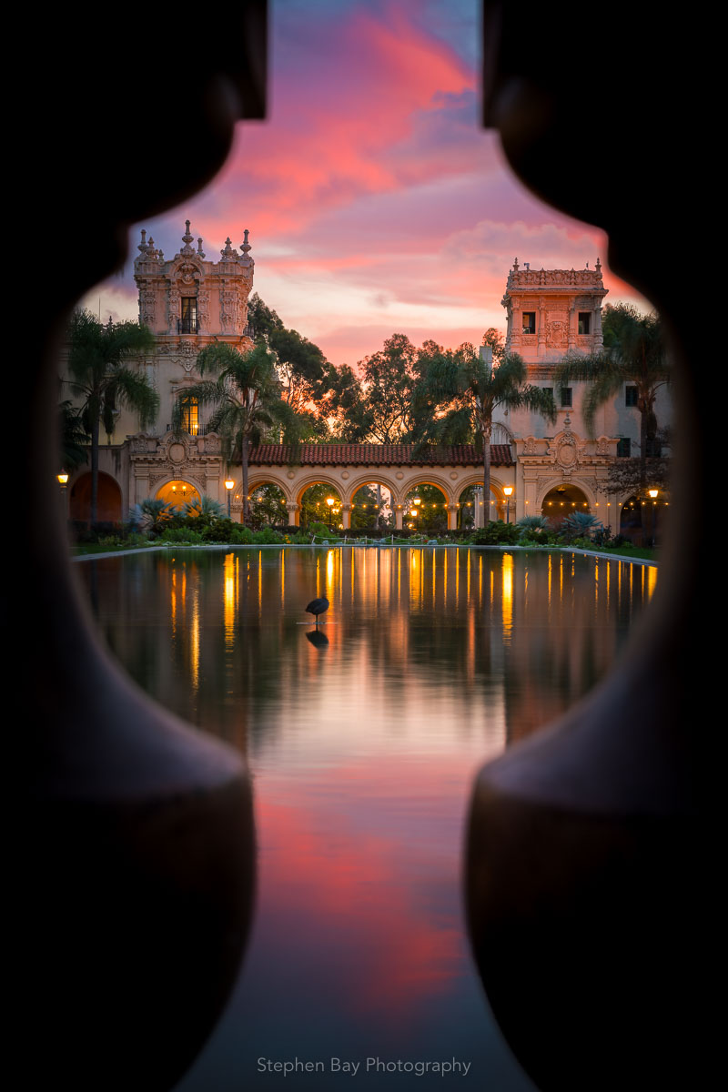Enchanted is a vertical photo of the Lily pond in Balboa Park by San Diego photographer Stephen Bay. The artwork shows the pond through the balusters on a small bridge creating a keyhole view. The sun has just set and fills the sky with pink and magenta tones which reflects into the pond. Casa de Balboa and the House of Hospitality can be seen at the far end of the pond.