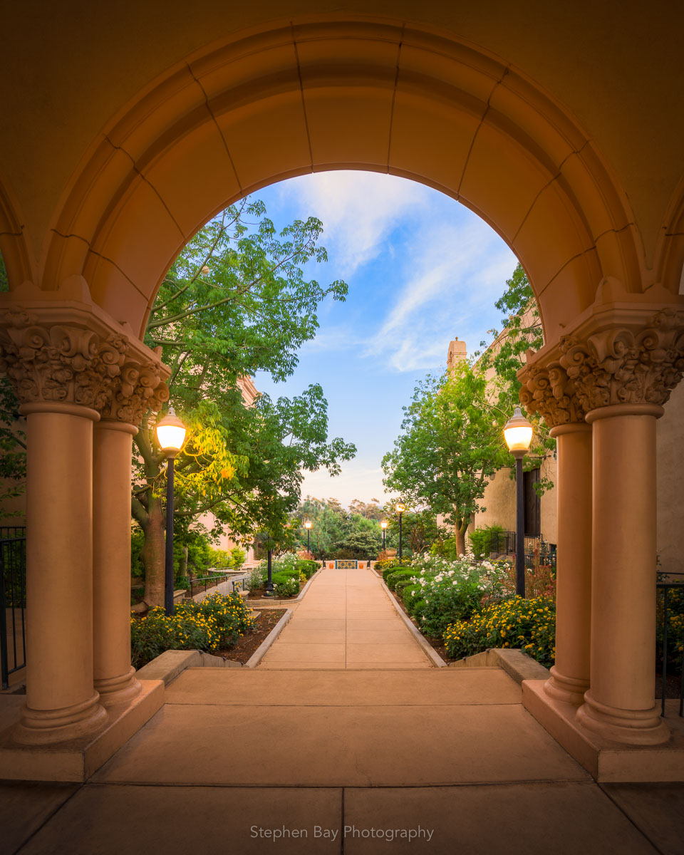 Twilight Forward is a photo of an arched opening surrounded by columns in Balboa Park with a pathway leading through it. Flowers line the path.