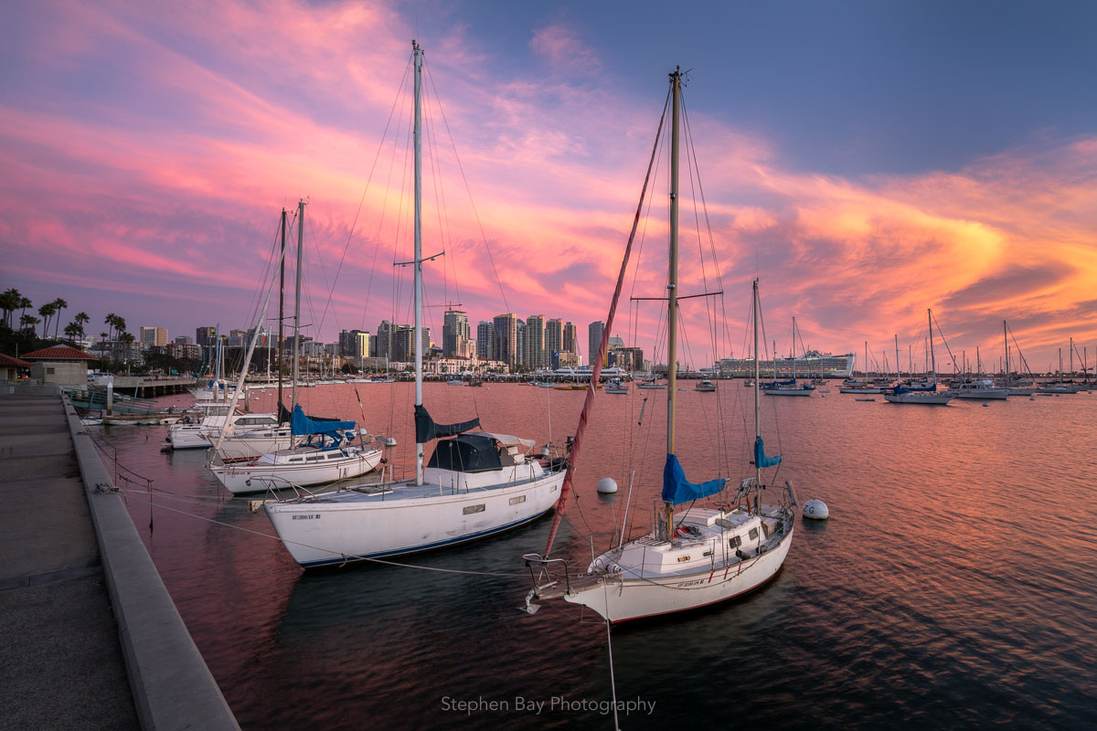 Sailboats moored along the Embarcadero.  The sky is a bright orange-pink from sunset.