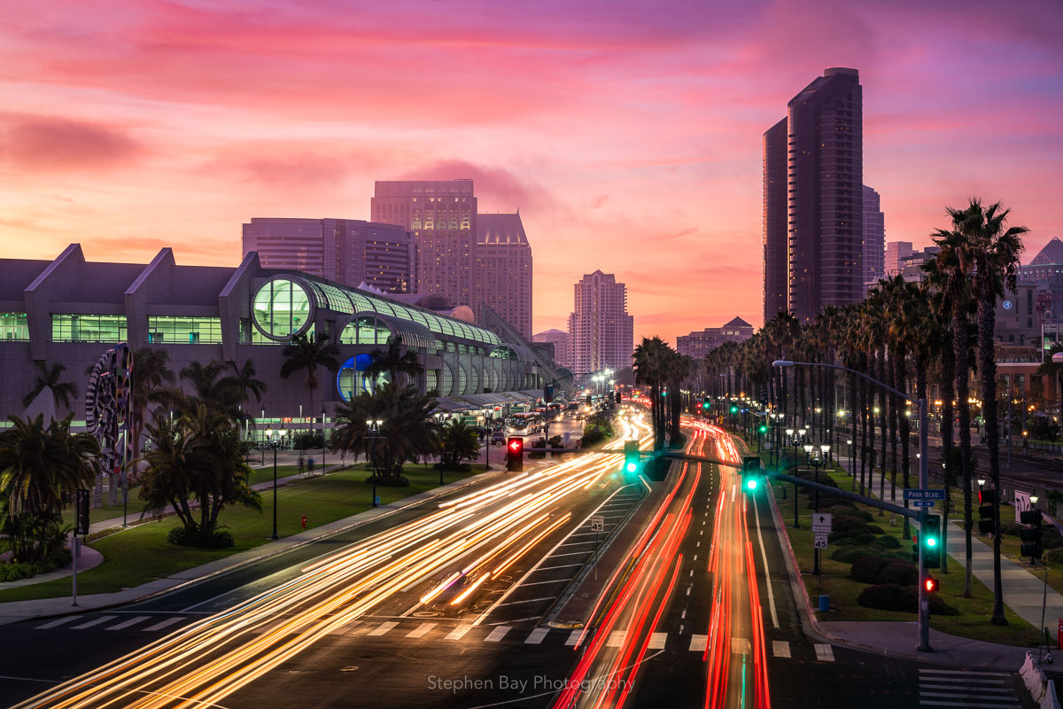 Sunset over downtown and harbor drive. The perspective is a slight aerial view and you can see the harbor drive leading off in to the distance with light trails from vehicles. The sky is misty pink as there is fog being lit up at sunset.
