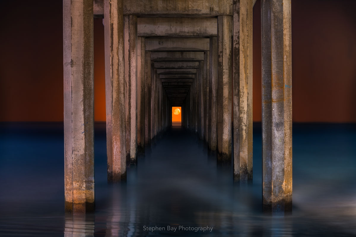 This is a view of Scripps pier from between the support pylons. The moon is setting and can be seen aligned in the center of the opening.