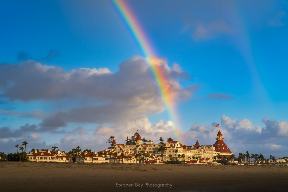 A photo of a rainbow over the Hotel Del Coronado. The arch of the rainbow comes down right in the center of the hotel. There is a blue sky and the photo was taken in the later afternoon with warm yellow light bathing the hotel.