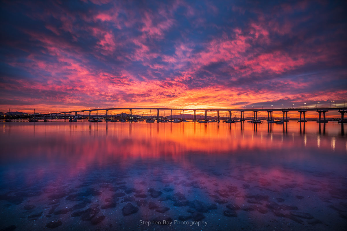Sunrise at Coronado Bridge. The water is still and rocks and shellfish can be seen underneath.