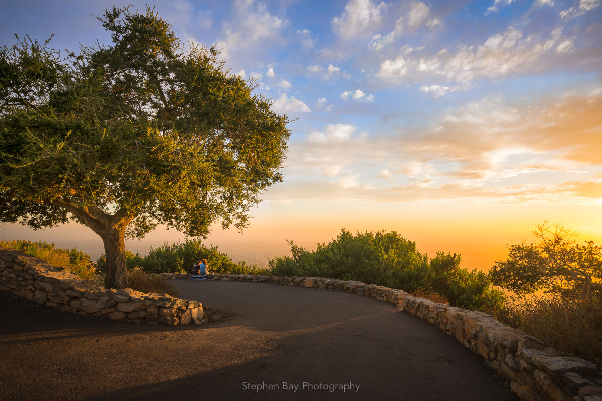 Simple Pleasures is a photo of Mt Helix Park in the late afternoon. There is a pair of friends sitting on the wall and enjoying a sunset at the park. The sky is full of clouds and there is an acorn tree beside a pathway that leads into the distance.